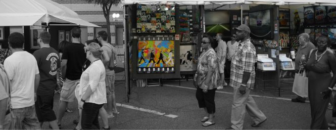 Festival attendees look on at a brightly colored painting