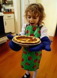 Portrait of a Girl Holding a Hot Pumpkin Pie.