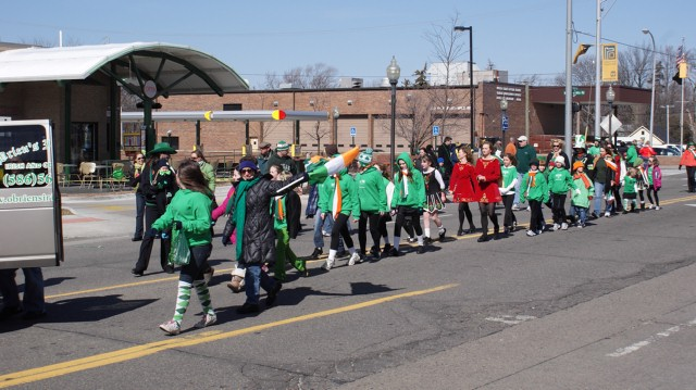 St. Patrick's Day Parade participants walking and throwing candy to the children.
