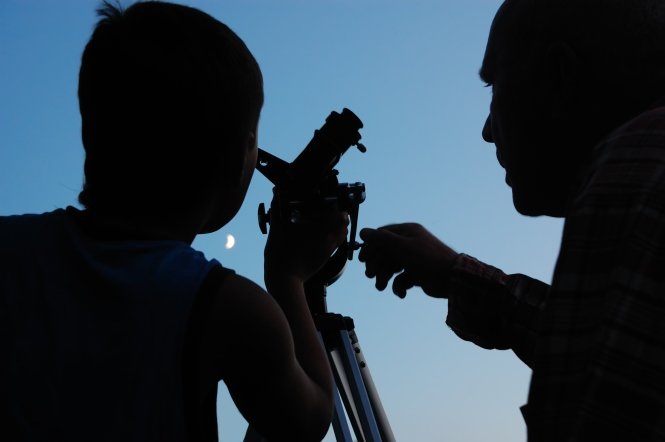 family discovering the moon with a telescope