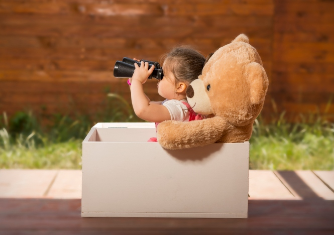 Beautiful little girl with binoculars inside white wooden box with toy bear exploring surroundings pretending to be on safari