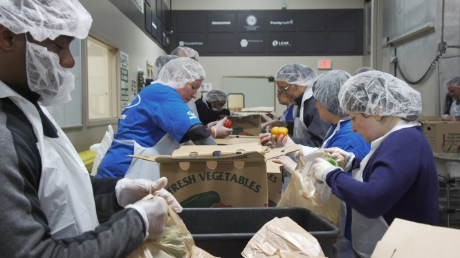 Volunteers pack food at the Forgotten Harvest Warehouse