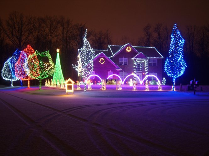 Beautiful house and yard decorated in many-colored lights, from red and blue to green and purple.