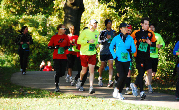 A group of runners jog down a paved path on a sunny fall day. The leaves on the trees at the edge of the trail are mostly green, just starting to change to fall colors.