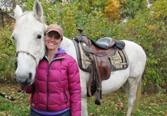 A woman smiles at the camera while she snuggles up against a white horse's neck. In the background, leaves are beginning to turn fall colors.