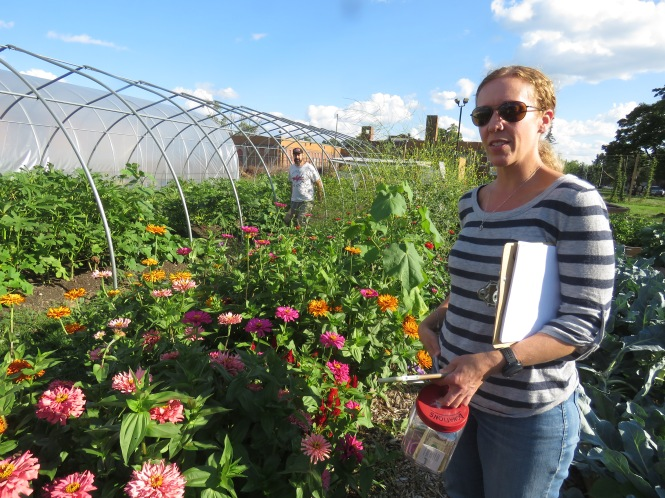 A woman stands next to zinnia plants in a community garden. She is holding a jar and clipboard with papers. A man is walking down the aisle of plots a bit further away.