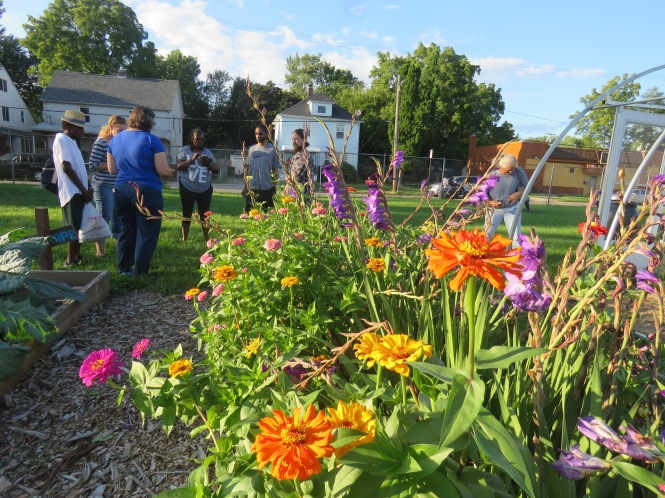 A group of people are gathered on the outer end of a community garden in a grassy area. Two two-story homes and a store are seen in the background. An array of colored flowers is seen in the foreground.