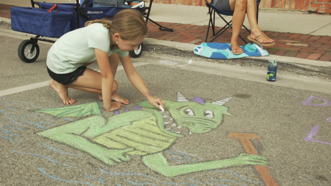 A young girl crouches down as she draws a dragon in chalk during Lake Orion's Dragon on the Lake Chalk Art Challenge.