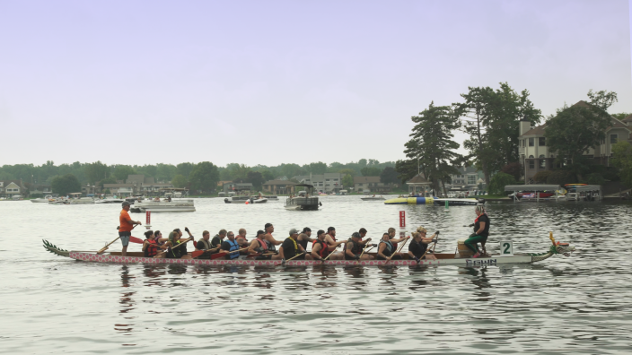 A dragon boat full of paddlers takes instruction from the captain at the front of the boat. Homes along the shoreline and boats can be seen in the background.