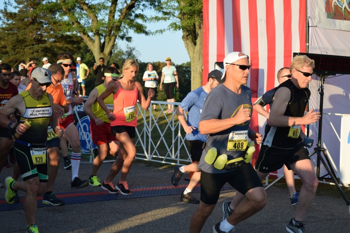 A group of runners, men and women, cross the starting line at the 2017 Brooksie Way Half Marathon race. Bystanders watch and cheer them as they stand under trees in the background. The sun is shining.