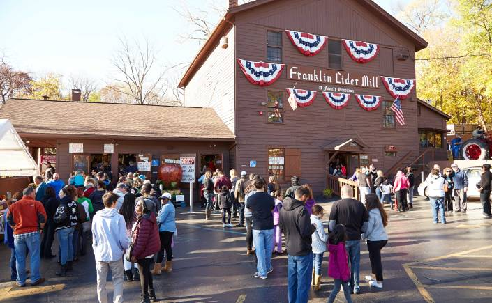A crowd of people gathers outside of Franklin Cider Mill on a sunny day. Trees with yellowing leaves stand behind the cider mill.