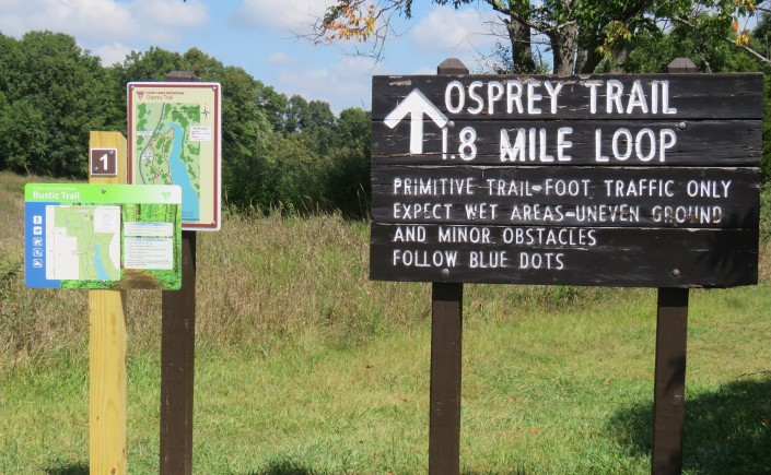 A photograph of three interpretive signs and their wooden posts in Stony Creek Metropark. Two smaller signs to the left show maps. A large dark brown wooden sign on the right shows an arrow pointing up. The text reads: Osprey Trail 1.8. Mile Loop. Underneath in a smaller font, it reads: Primitive Trail-Foot Traffic Only Expect Wet Areas-Uneven Ground and Minor Obstacles Follow Blue Dots