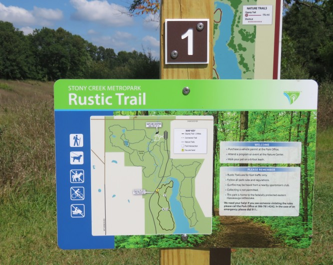 "A close up of an interpretive sign at Stony Creek Metropark. It is titled, Rustic Trail and shows a map and some text with the headings ""Welcome"" and ""Please Remember."" Trees can be seen in the distance and the sky above is blue with white puffy clouds."