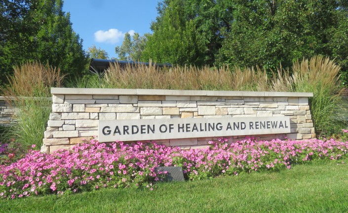 A sign crafted of light colored, rectangular tiles reads: GARDEN OF HEALING AND RENEWAL. Pink petunias have been planted in front of the sign and tall grasses have been planted behind it.