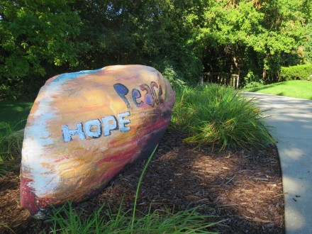 "A ""peace stone"" sits in a garden with the words, hope and peace showing. The rock is painted gold with text in varying colors."