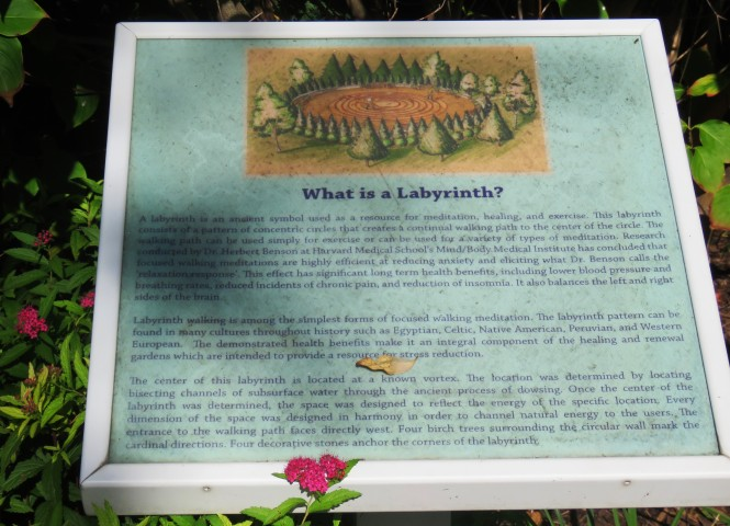 A white framed sign is posted in a garden. It reads: What is a Labyrinth? The sign is aqua blue in color and has three paragraphs of text. The edges of the photo show that flora and fauna around the sign.