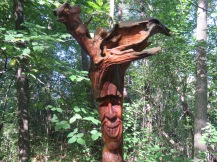 A wooden sculpture of a face bearing a toothy smile stands nestled among tall trees with green foliage.