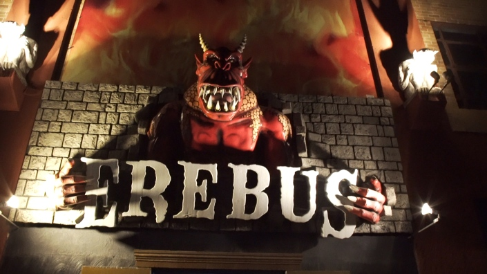 "A red colored demon comes out of a brick wall holding a sign that says ""EREBUS"". A mural of flames rises up behind the demon and gargoyles stand perched on each side of the demon."