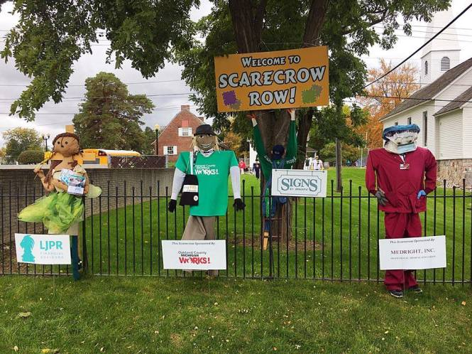 Three scarecrows lined up along a black wrought-iron fence. Signs in front show the businesses that decorated them. A sign hanging from a large maple tree behind the scarecrows reads: Welcome to Scarecrow Row!