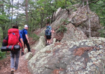 Hikers with heavy packs on their back walk up a steep trail through large boulders in the Blue Ridge Mountains in Virginia.