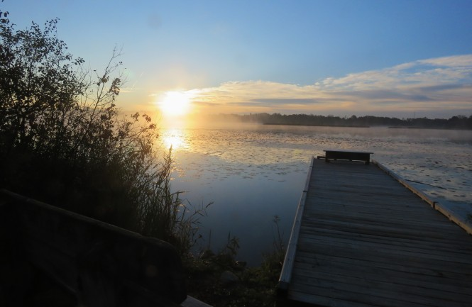 The sun rises over Lake Sixteen in Lake Orion. A portion of a wooden dock stretches from land and out over the lake. Fog rises up over the lake.