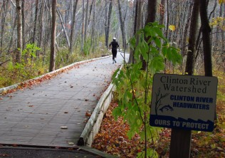 A jogger runs down a wooden bridge through the trees on a sunless day at Independence Oaks County Park.