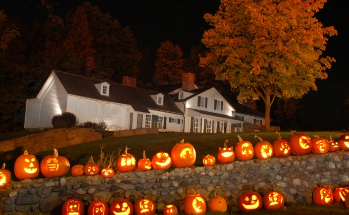 Lit Jack O' Lanterns lined up on a stone wall and in another line on the ground on a dark night. The white Van Hoosen Museum stands in the background next to a tree with orange foliage.