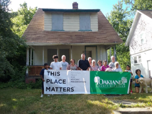 A group of people and an american doodle dog stand in front of a dilapidated bungalow in Pontiac, MI on a sunny day. They hold a banner in front of them. It is divided into two sections. The left side (white background) reads: This Place Matters | National Trust For Historic Preservation. The right side (green background) reads: Oakland County Michigan, and is surrounded by two trees.