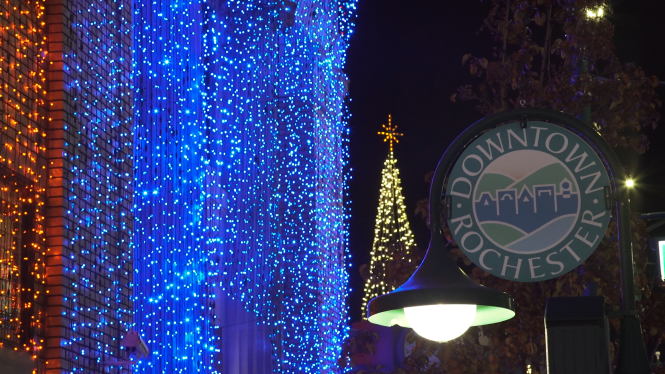 """Blue and orange lights are draped next to a lamp post labeled """"Downtown Rochester."""""""