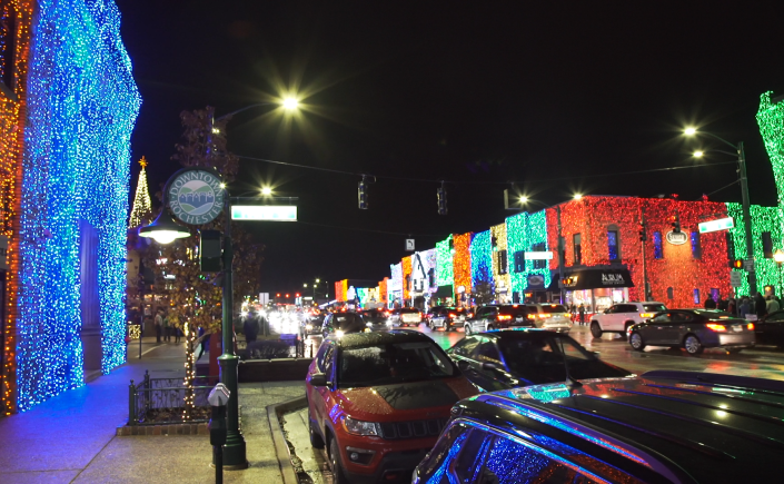 Wide shot of a decorated downtown covered in red, green, blue, and orange holiday lights.