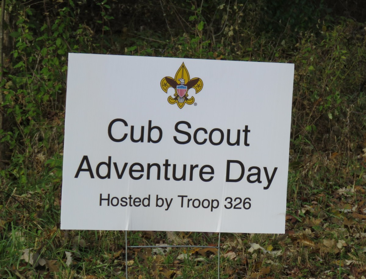 A white sign stick ups from the ground. It reads: Cub Scout Adventure Day Hosted by Troop 326.