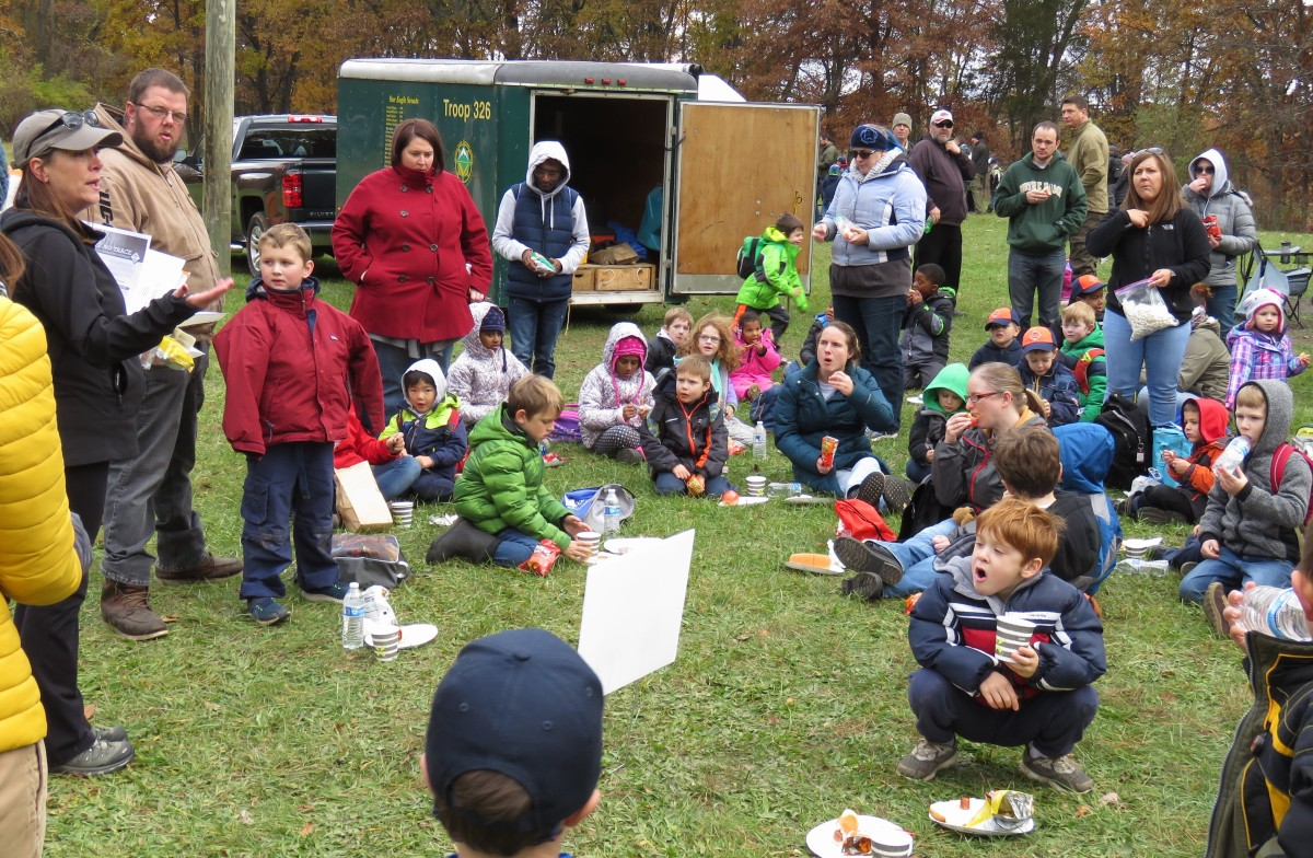 With their parents, a large group of Cub and Tiger Scouts enjoy a hot dog lunch gathered around their troop leaders on a patch of grass. Most of the adults are standing and the children are sitting. It's a gloomy, fall day. Trees stand in the landscape behind the group and a black pick-up truck and green trailer is parked nearby.