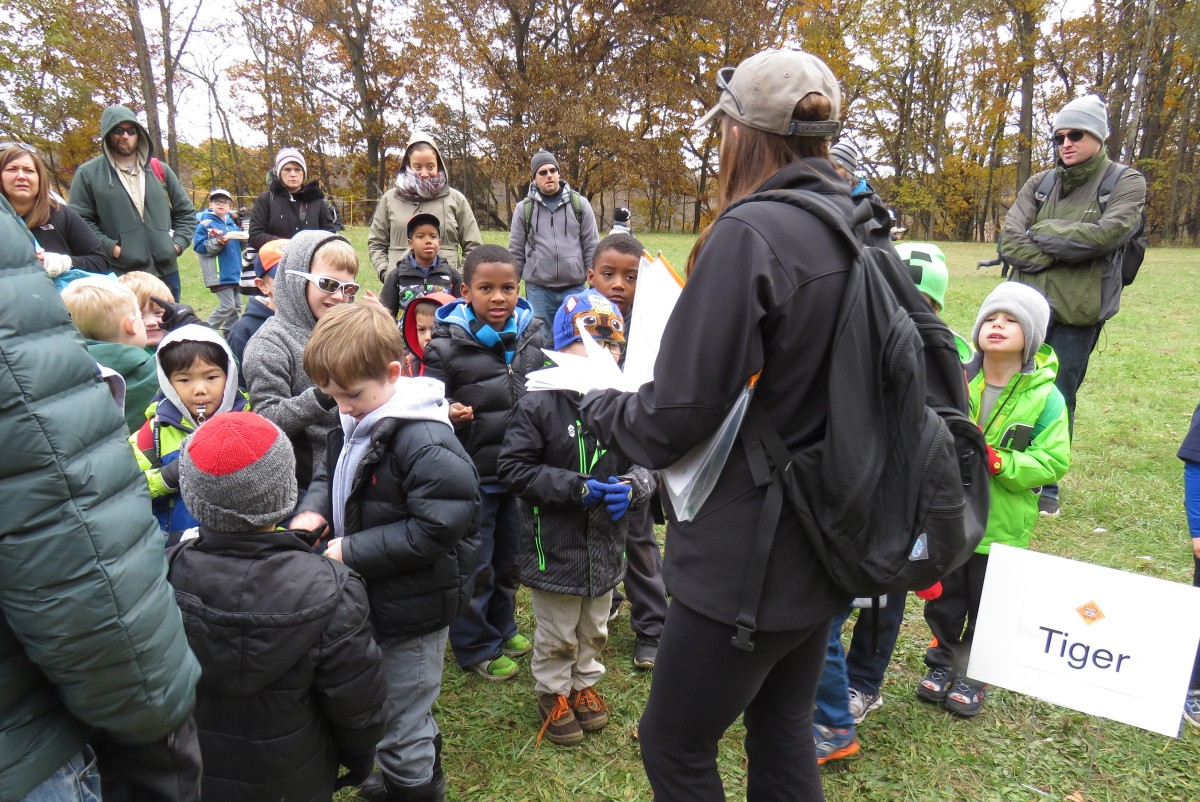 Children gather around as their scout leader hands out Scavenger Hunt worksheets.