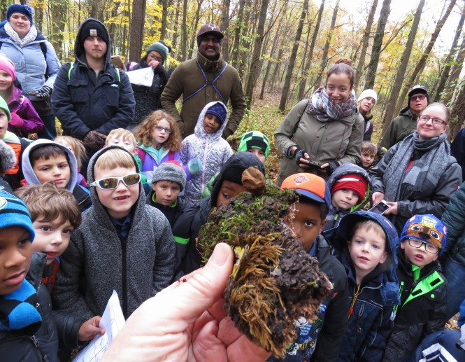 A crowd of scout (boys and girls) and their parents gather around the author (only his hand is in the image) as he hold up a piece of dirt and moss with a puffball mushroom attached to it.