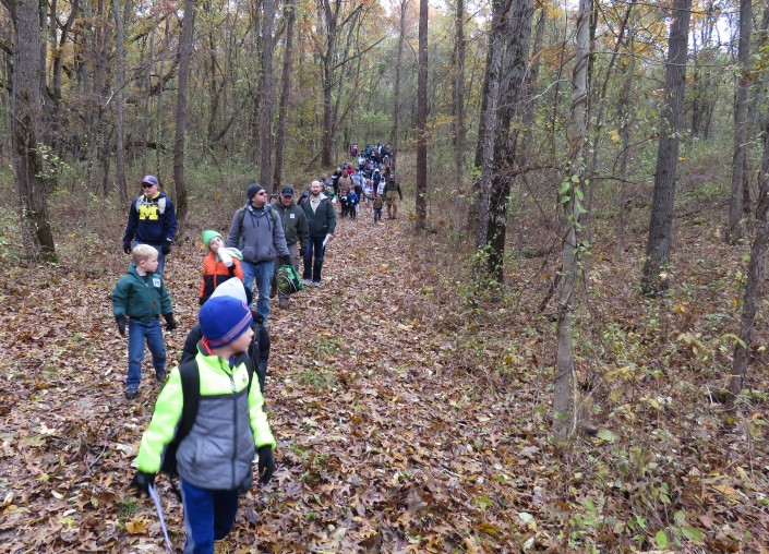 A long line of cub scouts, tiger scouts, and their families walk through a leaf covered, dirt trail in the woods.