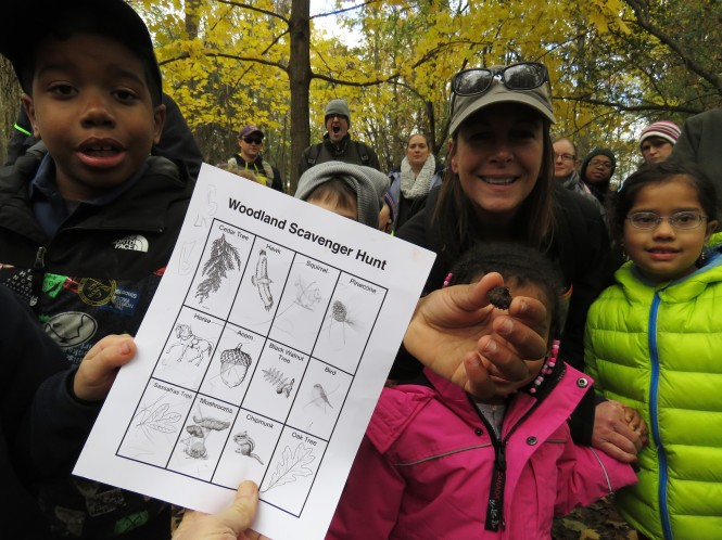 A photo of a Woodland Scavenger Hunt worksheet. An smiling boy, standing with a group of children and the scout leader, holds up an acorn behind it. The worksheet is printed on white paper with black ink and shows an illustration of 12 items in 3 rows with 4 items each going across.
