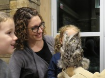 A smiling woman and small child observe an Eastern Screech-Owl that is perched on a gloved hand. The owl is small, with short ear tufts and dark bill. It is gray overall with dark vertical streaks and fine dark barring. It has large yellow eyes.