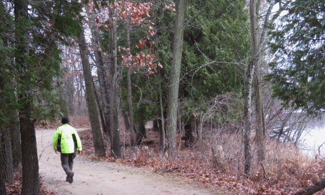A man, photographed from behind, walks down a winding, dirt path through trees. He is wearing a neon yellow jacket and black winter hat.
