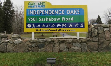 A colorful sign of the entrance of a park sits on a rock ledge. It reads Oakland County Parks, Independence Oaks, 9501 Sashabaw Road. It shows icons for various outdoor activities like hiking, skiing, biking, and more. The website: OaklandCountyParks.com is listed at the bottom of the sign.