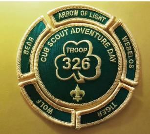 A round Cub Scout Adventure Day patch. It has the words Troop 326 enclosed in a clover. Separate patches with the words bear, arrow of light, webelos, tiger and wolf encircle the center patch. The patches are dark green with gold text and also trimmed in gold.