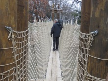 A man walking on a suspension bridge.