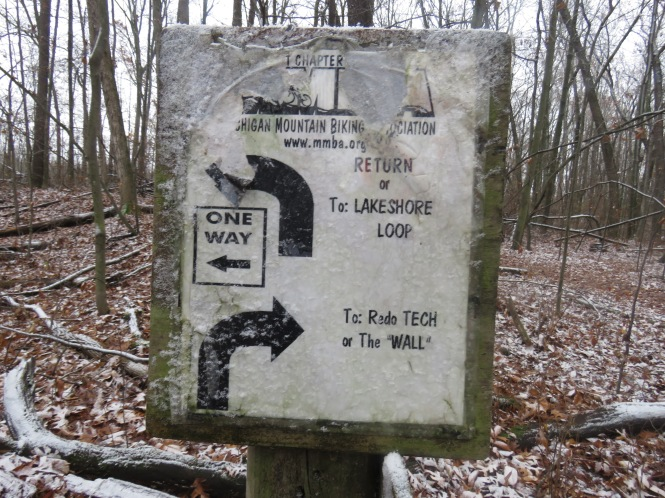 """A trail marker with a ragged sign that has arrows pointing to RETURN or Lakeshore Loop, and Redo TECH or The """"Wall."""""""