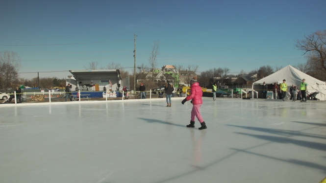 People skate on a clean skating rink in the outdoors.