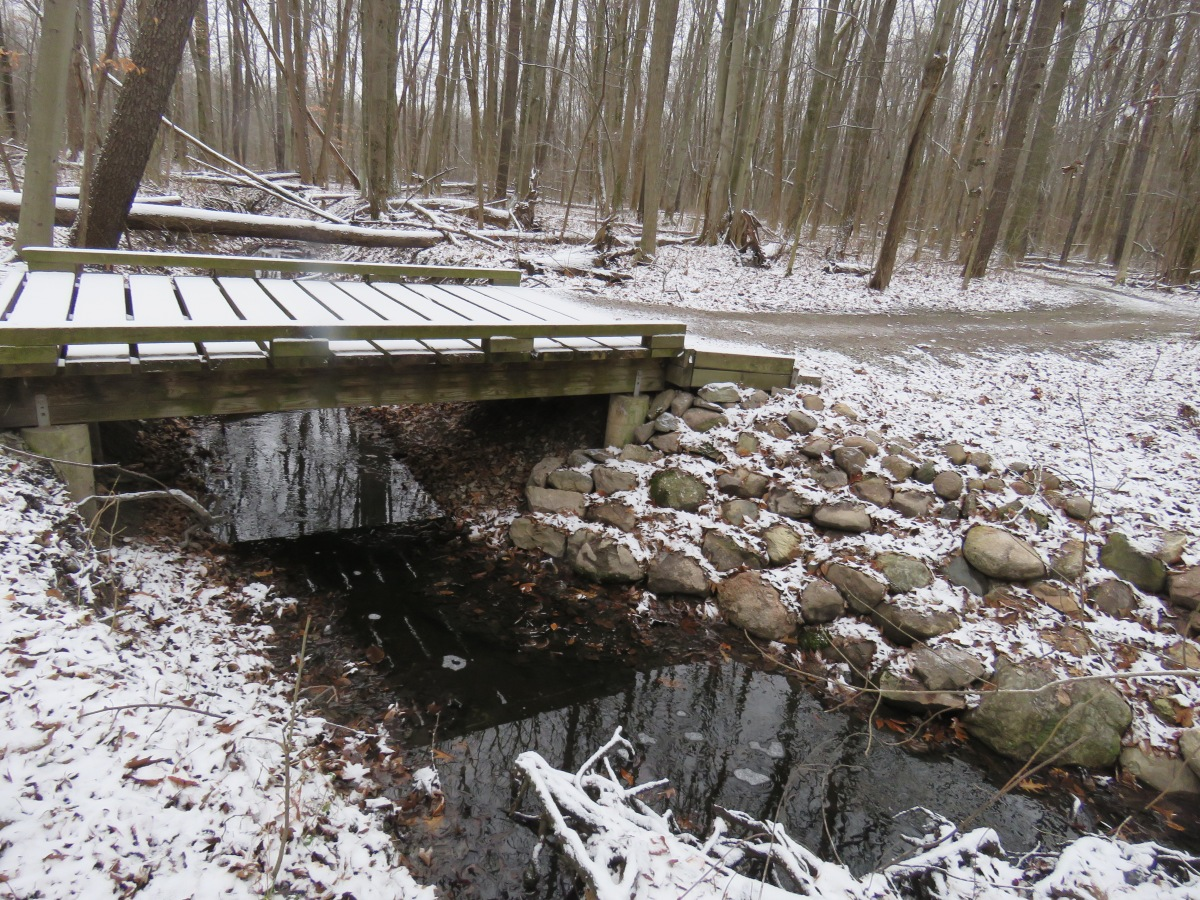 A snow covered wooden bridge over a creek