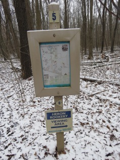A park map posted in the woods. It has a sign beneath it pointing to the Heron Rookery Viewing Area.