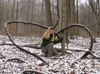 A grapevine that formed a nearly perfect woodland heart. A woman with blonde hair poses for a photo crouched down inside of it.