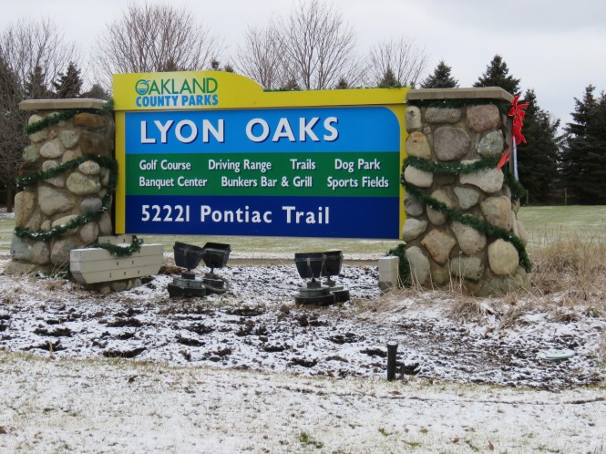 A large sign reads: Oakland County Parks, Lyon Oaks 52221 Pontiac Trail. Amenities listed on the sign are: Golf Course, Banquet Center, Driving Ranet, Bunkers Bar & Grill, Trails, Dog Park, and Sports Fields