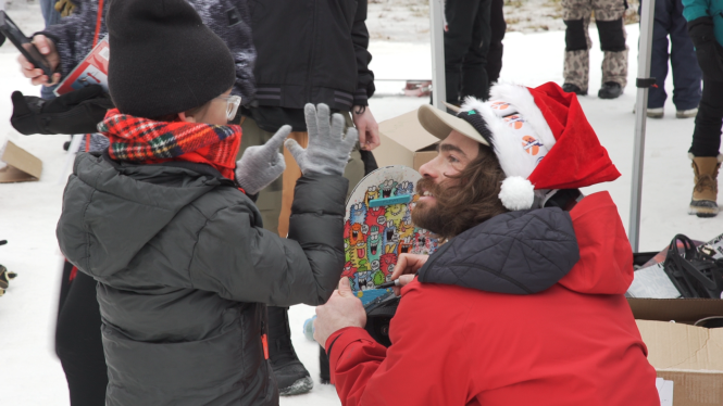 Danny Davis signs a young fan's snowboard.