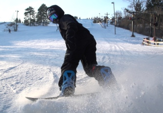 Snowboarder kicks up snow as they stop at the bottom on the slopes.
