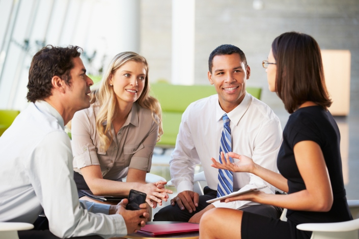 Four business people talk around a small coffee table.